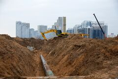 Free Excavator At Construction Site During Laying Sewer And Main Reticulation Systems. Civil Infrastructure Pipe, Water Lines, Sanitary Stock Images - 175921944