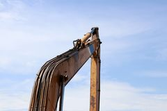 Excavator or backhoe bucket arm in yellow color on blue sky background. royalty free stock photography