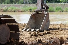 Excavator or backhoe bucket on the soil floor. stock photo
