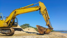 Excavator on the beach fixing up erosion. On the beach front royalty free stock images