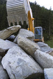 Excavator behind large rocks Royalty Free Stock Photos