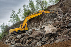 Excavator behind the slope. Royalty Free Stock Photography