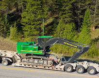 An excavator being taken to a construction site by road Royalty Free Stock Image