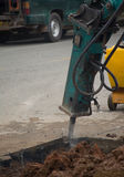 Excavator breaking and drilling the concrete road . Royalty Free Stock Images