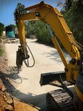 Excavator breaking and drilling the concrete road for repairing. Drill concrete machine and Drilling Machinery at Work Royalty Free Stock Photos