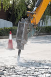 Excavator breaking and drilling the concrete road for repairing Royalty Free Stock Images