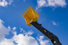 Excavator bucket on blue sky background royalty free stock photos