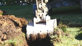 Excavator with bucket on a building site. Excavator with bucket digging a trench on the grass in slow motion stock video