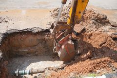 Excavator bucket  bulldozer work a hole the repair of pipe water Royalty Free Stock Photography
