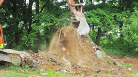Excavator bucket clears the site of debris. stock video footage