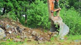 Excavator bucket clears the site of debris. stock video