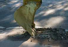 Excavator bucket destroys asphalt. Preparation for road repair works Royalty Free Stock Photography