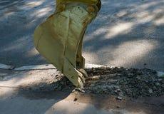 Excavator bucket destroys asphalt. Royalty Free Stock Photography