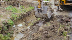 Excavator bucket digging a drainage ditch on a construction site. stock video footage