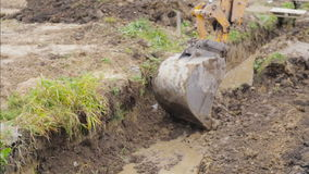 Excavator bucket digging a drainage ditch on a construction site. Building. stock video