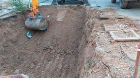 Excavator bucket digging a hole at construction site stock video