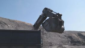 An excavator bucket digs coal. And pours it into a truck in a open pit stock video footage