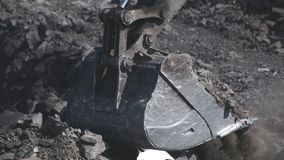 An excavator bucket digs coal. And pours it into a truck in a open pit stock footage