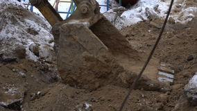 Excavator bucket digs the ground stock video