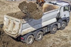 Excavator bucket full of dirt and truck Royalty Free Stock Image