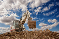 Excavator with bucket on gravels Stock Photography