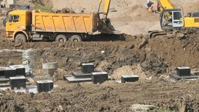 Excavator with bucket pushes dump truck from mud. Excavator with its bucket pushes yellow dump truck from the mud on a construction site in the summer season stock footage