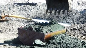 The excavator bucket spreads the bulk of the soil in an iron container stock footage