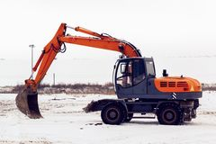 Excavator with a bucket standing in a snowy field royalty free stock photography