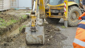 Excavator bucket tamps soil. Construction site. stock video footage