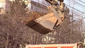 Excavator bucket unloading. Material to a dumping truck at construction site stock video