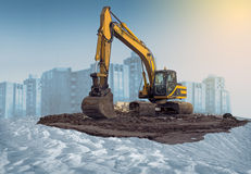 Excavator. Bucket wheel excavator working on new housing project. Winter time landscape, Modern houses and clear blue sky at the background Royalty Free Stock Photos