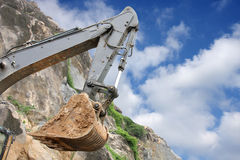 An excavator bucket on work in a granite mine Stock Photo