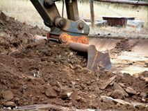 Excavator bucket at work. Excavator at work moving and digging dirt with soil earth works construction in new housing development subdivision. Earth mover bucket Royalty Free Stock Photography
