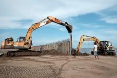Excavator build breakwater at beach Stock Image