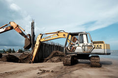 Excavator build breakwater at beach Royalty Free Stock Images