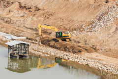 Excavator building the bank to prevent riverside erosion Stock Images