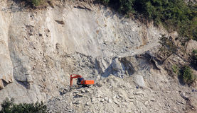 Excavator building the road on a steep slope royalty free stock images