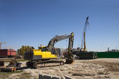 Excavator at building site under construction against the blue sky - Image with copy space royalty free stock photos