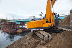 Excavator builds a bridge. Stock Photography