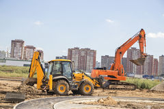 The excavator and the bulldozer carry out earthwork. In the new city residential district Stock Image