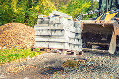Excavator or bulldozer carrying pallets with paving stones or sidewalk borders Stock Images