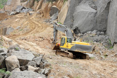 An excavator carrying a oil drum in a granite mine Stock Images