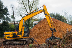 Excavator with Clamshell Grab Bucket used to move wood chips Stock Photo