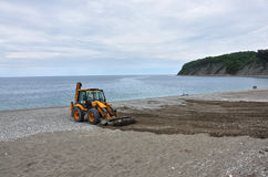 Excavator cleans the beach Stock Photos