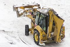 An excavator cleans snow blocked parking Stock Photography