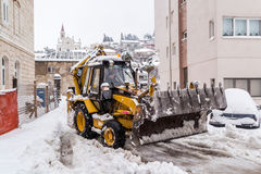 Excavator cleans the streets of large amounts of snow Stock Image