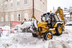 Excavator cleans the streets of large amounts of snow Royalty Free Stock Photo