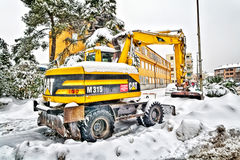 Excavator cleans the streets of large amounts of snow Royalty Free Stock Images