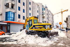 Excavator cleans the streets of large amounts of snow Stock Photos