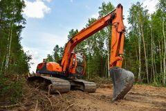 Excavator clearing forest for new development. Orange Backhoe modified for forestry work. Tracked heavy power machinery for forest